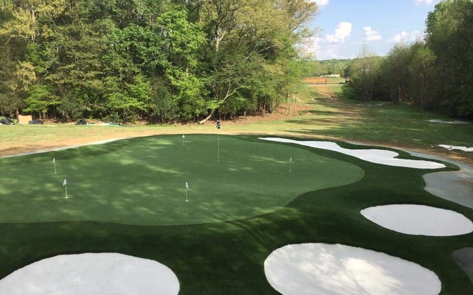 artificial grass putting green with multiple sand bunkers