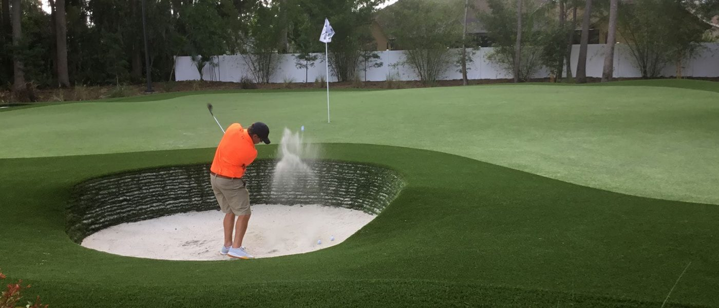 Man trying to get out of sand trap on personal backyard putting green
