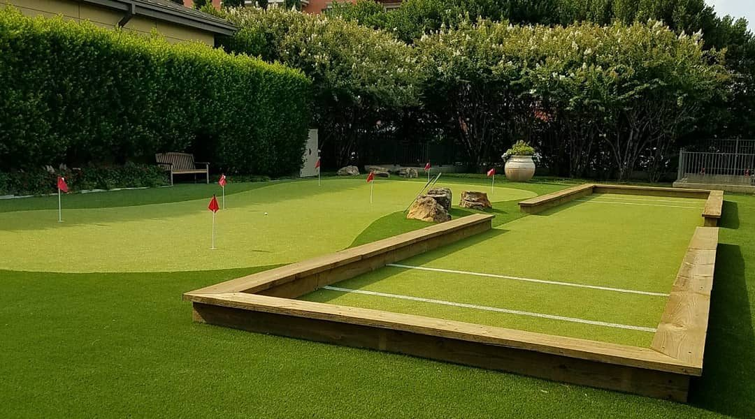 artificial grass boccee ball court with putting green in the background