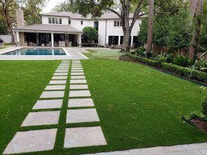 private estate with putting green and pavers surrounded by artificial grass lawn