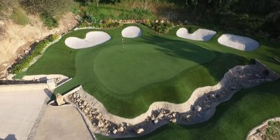 private artificial grass golf green with white sand bunkers